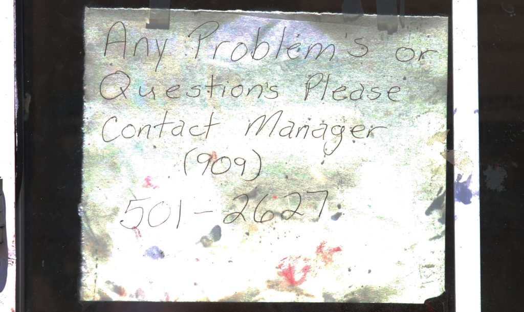 Photo/Anthony Victoria: A sign posted outside the manager's office at the Cedarwood Apartments.