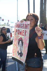 """Photo/Anthony Victoria: Immigrant rights advocate Erika Paz showing solidarity by holding a sign that reads, """"Immigrant Power."""""""