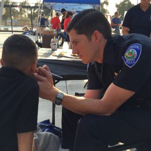 Photo/Monica Lagos: A San Bernardino Police officer paints the face of a young boy during the National Night Out event at Nunez Park on August 2. The annual event is an effort to emphasize community collaboration and bring together residents.
