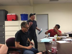 Courtesy Photo: Veteran Jerry Donovan Smith engaging with CSUSB student and U.S. Marine Juan Hernandez during a Dialogues on the Experience of War meeting back in July, right. Left, San Bernardino Valley College English Professor Joe Notarangelo browses the text