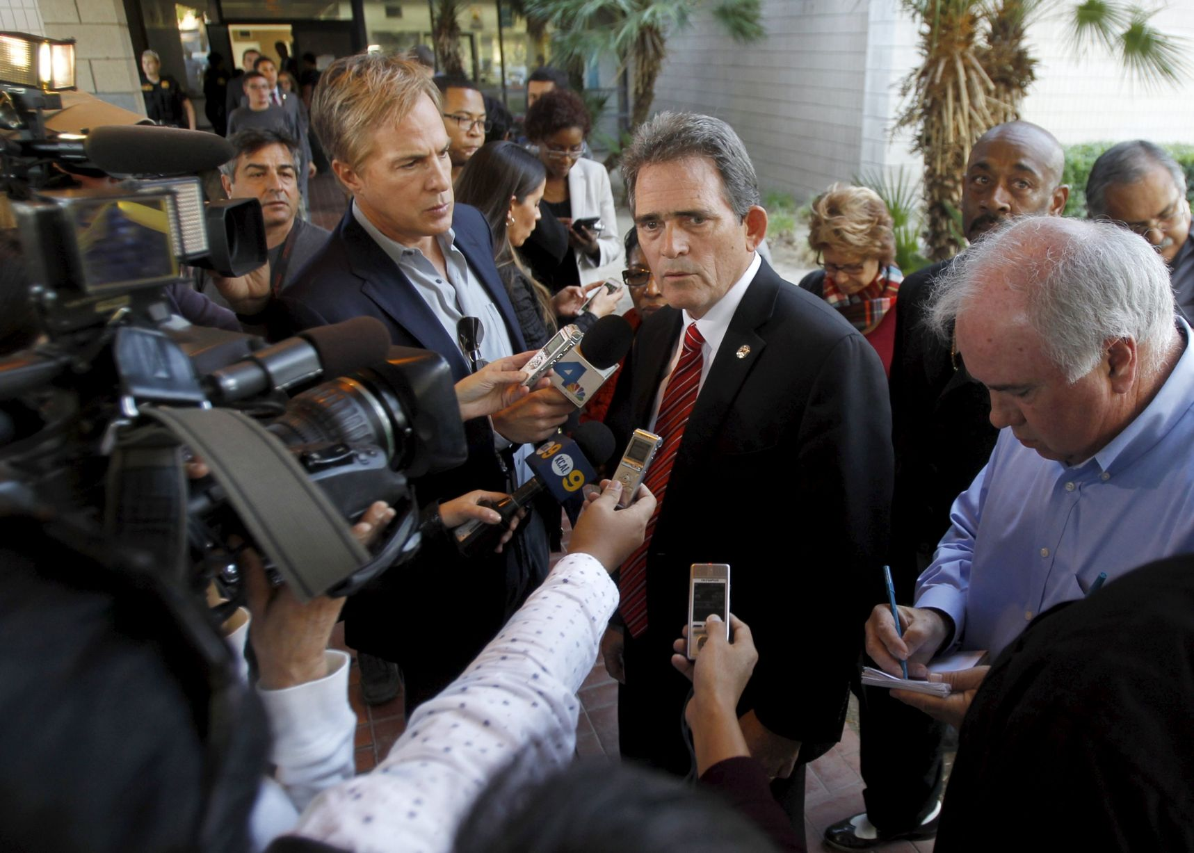 Photo/Reuters: Mayor Carey Davis, center, speaking to the media outside the Rudy Hernandez Center on December 2, 2015.