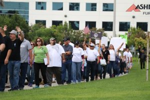 Photo/Anthony Victoria: Hundreds of people protesting outside Ashley Furniture offices in Colton.